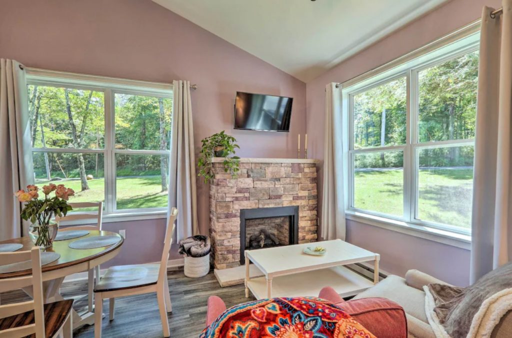 The interior of a cabin that has pale dusty pink walls, a light stone fireplace, large windows, chairs, a coffee table, and a dining room table.