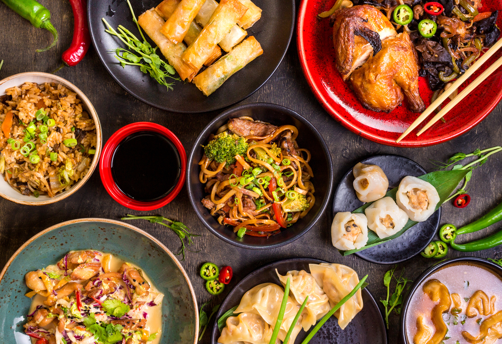 An overhead image of red and black plates full of Chinese food like the food you can get at one of the best restaurants in Philadelphia. There is rice, noodles, dumplings, spring rolls, chicken, peppers, soy sauce, and chopsticks.