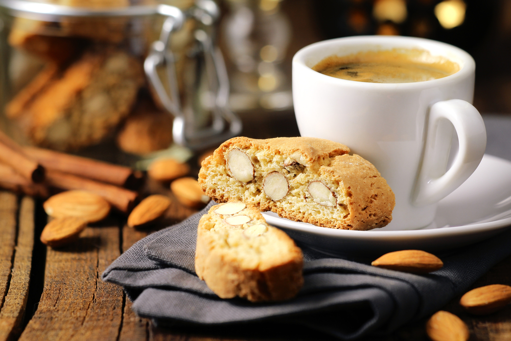 A almond scone sitting on black napkin and on a saucer. There is a coffee cup on the saucer as well and it is filled with a coffee that has a frothy top. The cup and saucer are white.