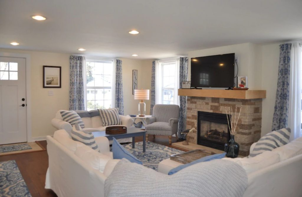 The living room of a cabin in Edinboro Pennsylvania. There are white couches with blue and white stripped pillows, a chair, lots of windows, and a brown brick fireplace with a tv on the mantle.