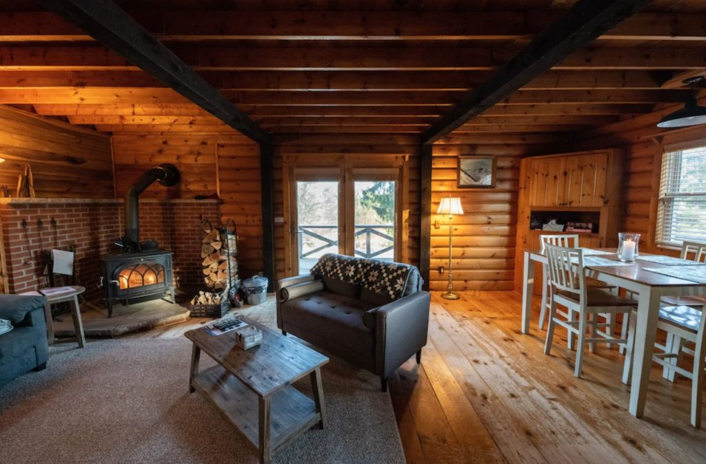 The interior of a rustic log cabin in PA. There is a wood-burning stove, a living room, a dining area, and double doors with windows.