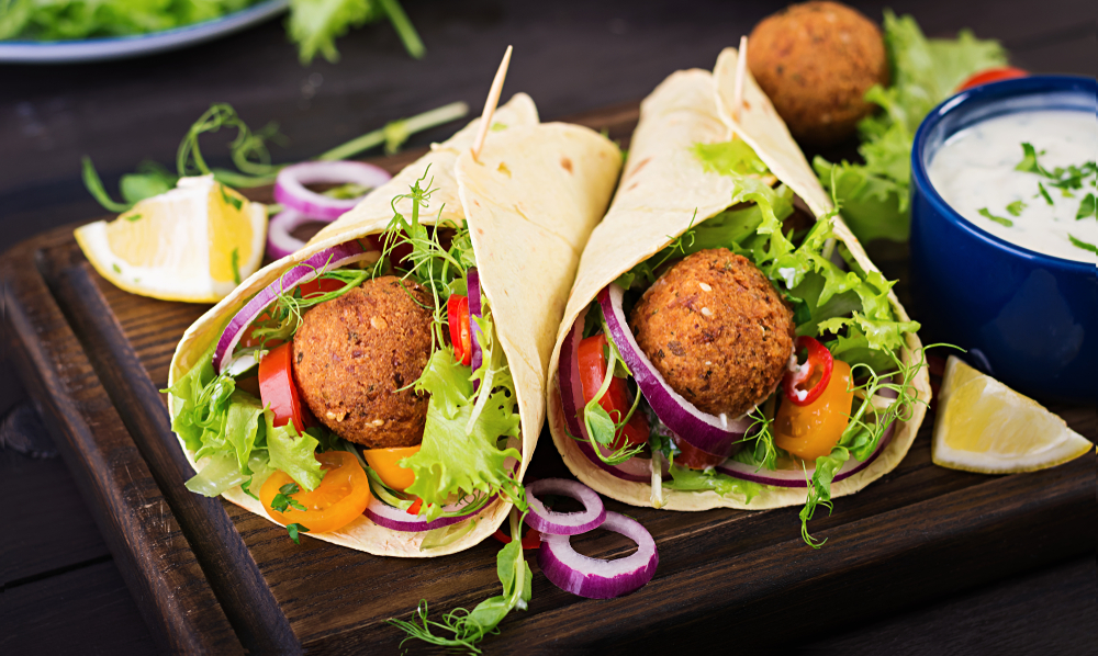Two falafel wraps like the kind you can find at one of the best restaurants in Philadelphia. Inside the wrap there are falafel balls, lettuce, onions, peppers, and other vegetables.