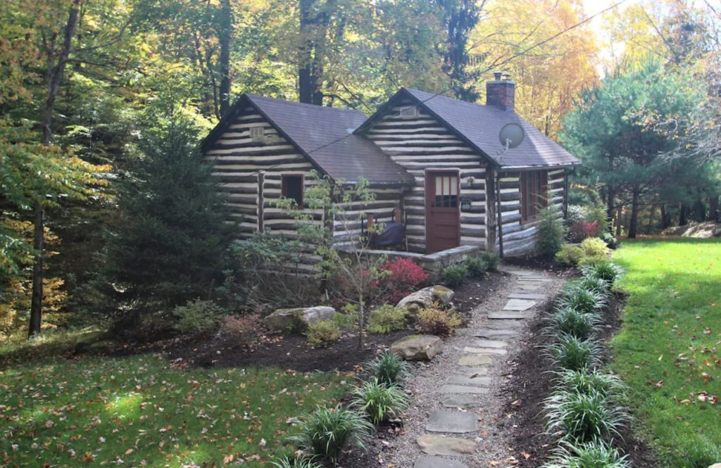 A classic log cabin surrounded by dense trees, a small lawn, and a small garden. There is a stone path that leads to the front door of the cabin.