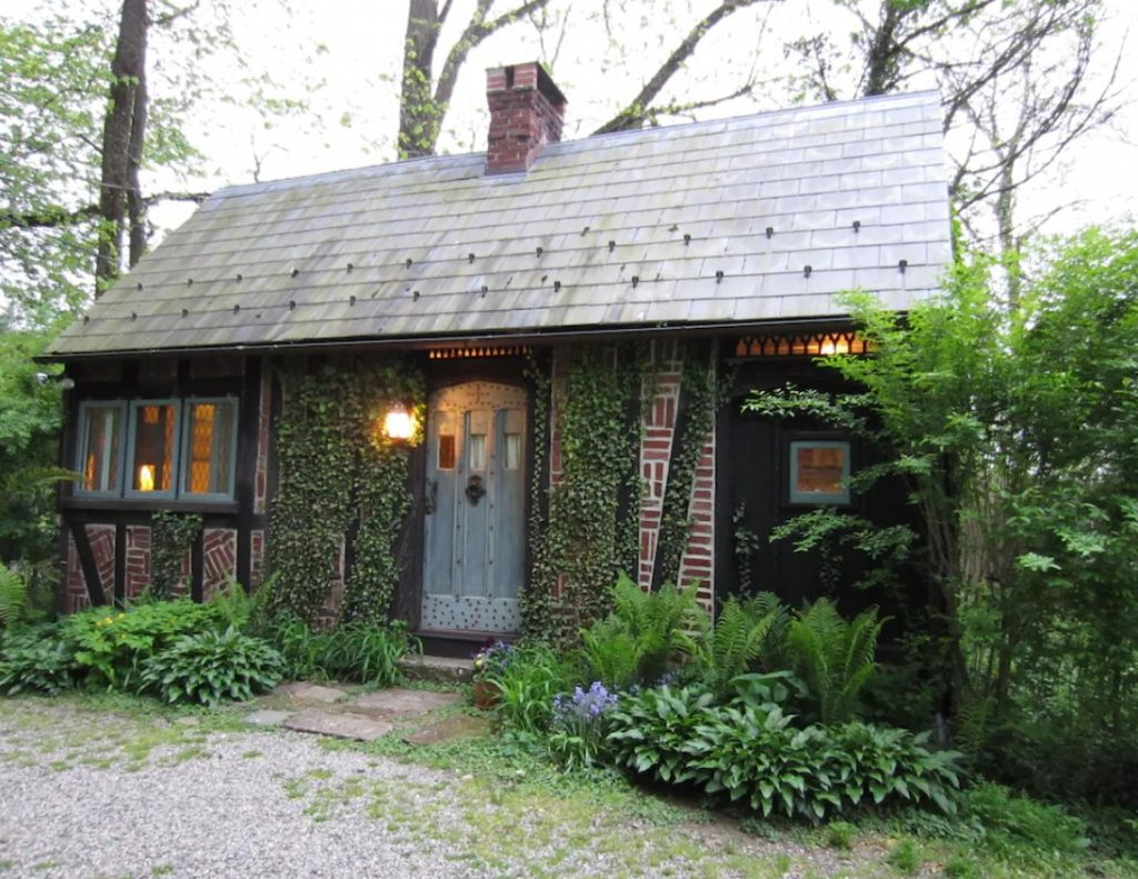 The exterior of a charming cabin made of brick laid out in a herringbone pattern. It has a slate roof, a light gray door, and is surrounded by lush greenery. It's one of the cutest cabins in PA