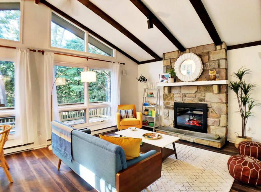 The interior of one of the nicest cabins in Pennsylvania. It has a large stone fireplace, mid century style furniture and décor, tall ceilings with wood beams, and large windows.
