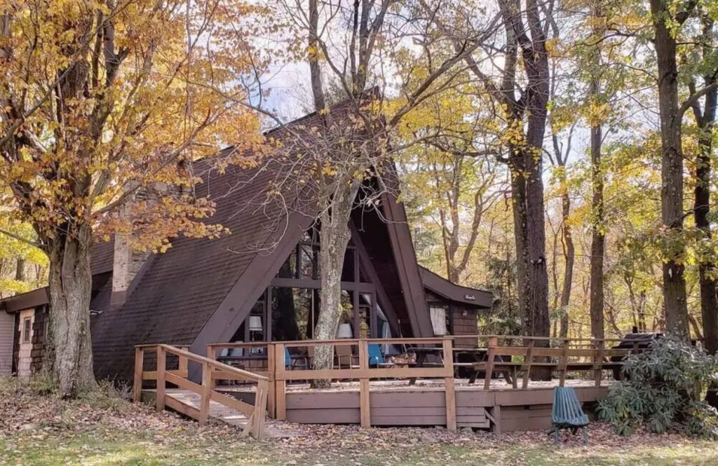 A classic A-frame cabin in the woods of PA. It has a large deck in front of it with a picnic table and chairs. There are large windows on the front of the cabin.
