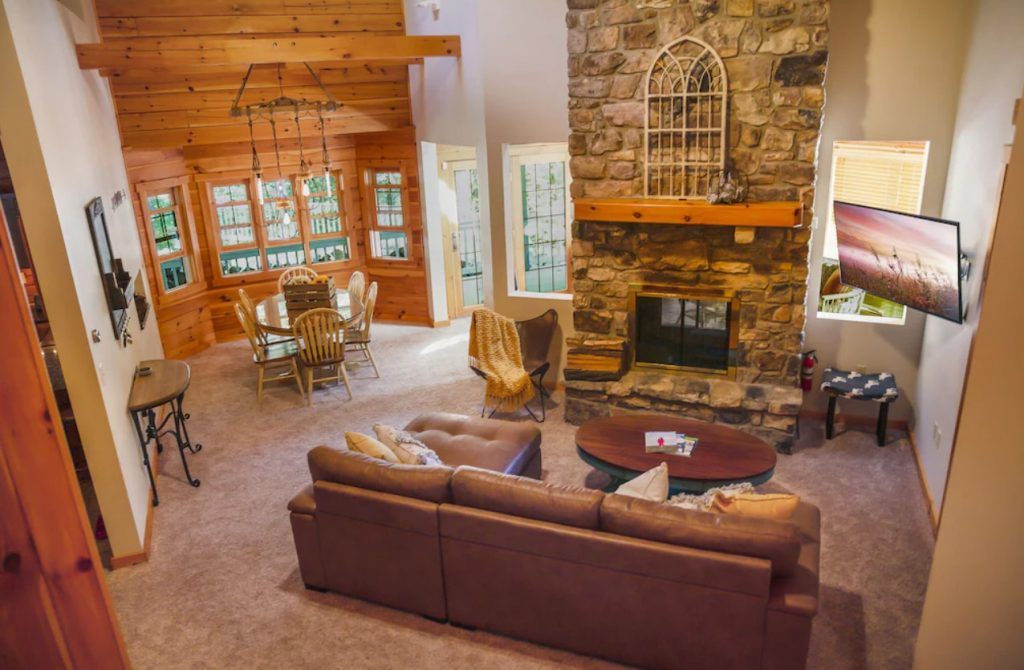 The living room of a cozy cabin in PA with a large stone fireplace, carpet, a leather sofa, tv, dining table, and lots of windows.