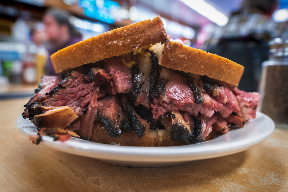 A large sandwich on a small white plate. It is overflowing with beef with charred tips and you can see some cheese. It is on a slice of what looks like white bread.