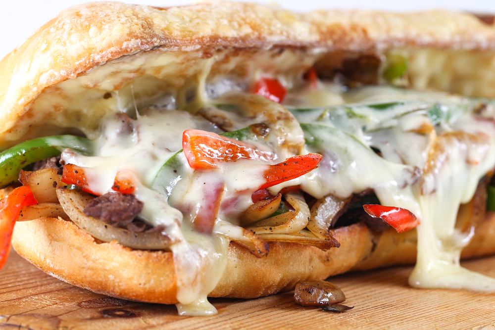 A close up of a cheesesteak like one you can find at one of the best restaurants in Philadelphia. It has beef, onions, peppers, mushrooms, cheese, and is on a toasted bun.