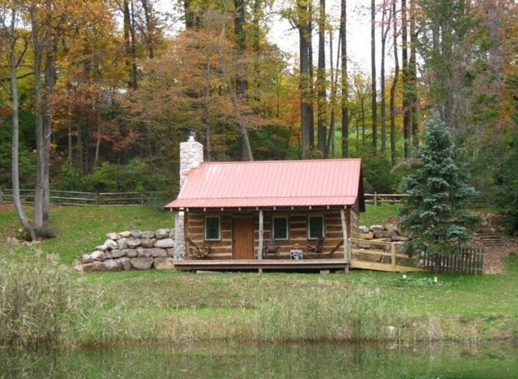 The exterior of a small restored 1800s log cabin. It has a small front porch and looks out onto a small pond. Behind it is dense forest and it is surrounded by a green hilly lawn.
