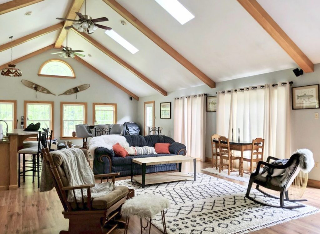 The interior living room of a large secluded river cabins in PA. There is a sitting area with a couch, chairs, and a small dining table. You can also see a kitchen bar, lots of windows, and tall ceilings with wood beams.