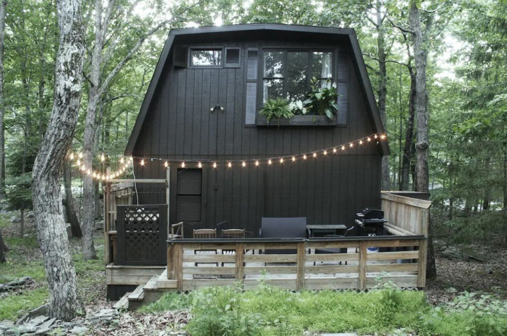 The exterior of a black or dark brown cabins in Pennsylvania in the middle of the woods. The cabin has a large window on the top floor and a deck with chairs, a grill, and string lights.
