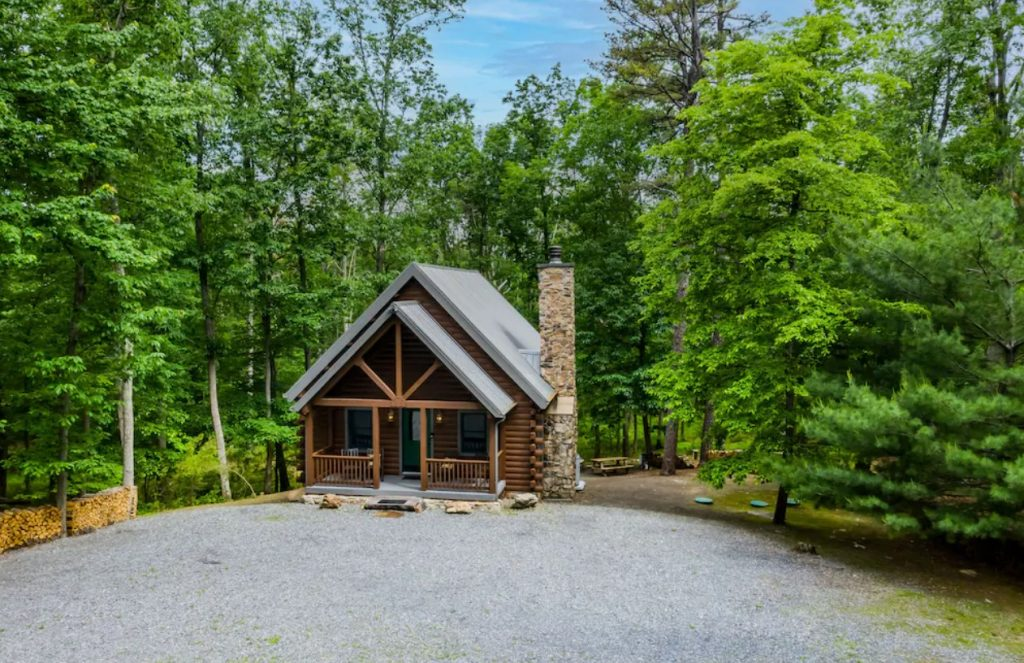 A charming log cabins in Pennsylvania nested in the woods. It has a large stone chimney, a small front porch, and a gravel driveway in front of it.