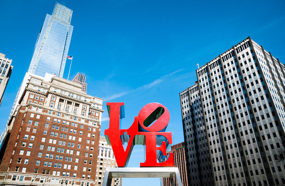 Looking up at the famous LOVE sculpture in LOVE Park. It is a bright red statue with the LO stacked on top of VE. In the background you can see part of the Philly skyline.
