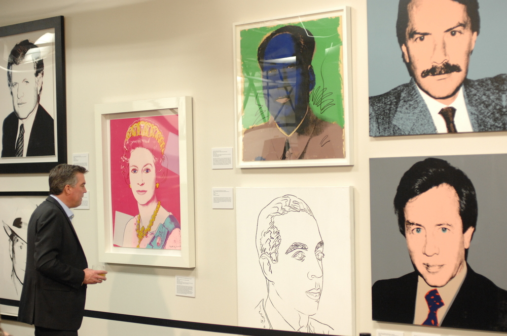 A person looking at a collection of Andy Warhol paintings and photographs. There are images of men, drawings of men's profiles, a pop art image of Queen Elizabeth, and other items on display. Its one of the best things to do in Pittsburgh.