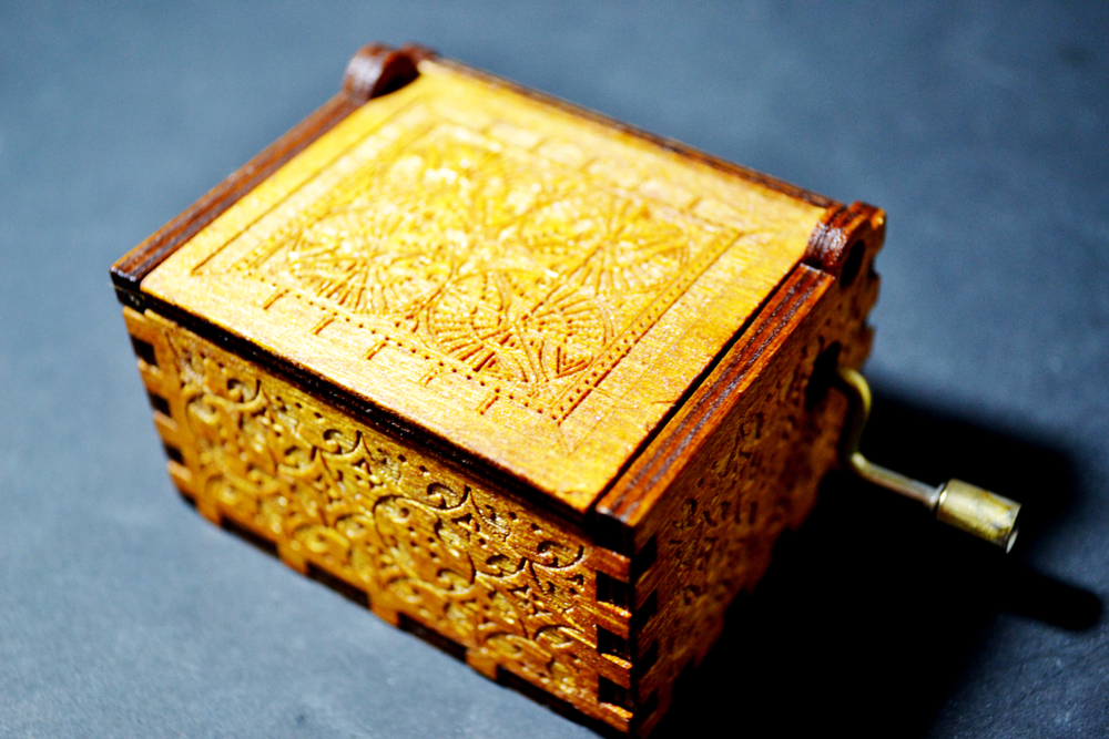 A close up of an intricately carved antique music box with a worn bronze handle.