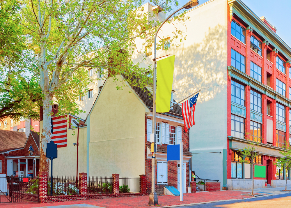 The exterior of a small house that is believed to be where Betsy Ross stitched the first American Flag. It is a very small brick building with white windows and doors and a small brick courtyard. There is a large tree in the courtyard and modern buildings around it.