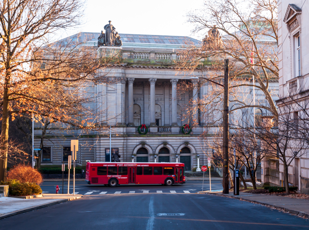 The exterior of a grand building that is the Carnegie Museum of Natural History. In front of it is a red bus and it is surround with trees with no leaves.