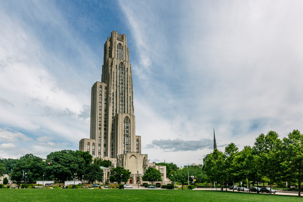 The exterior of the Cathedral of Learning, a super tall building on the campus of the University of Pittsburgh. It has gothic style architecture and in front of it is a large green lawn. Its one of the best things to do in Pittsburgh.