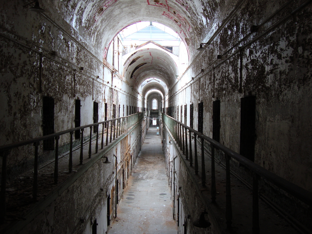 Looking down a long hallway in a dilapidated prison. There is paint peeling off of the walls, part of the hallway are dark, and it is two floors with rows and rows of cell doors. Its one of the best things to do in Philadelphia.