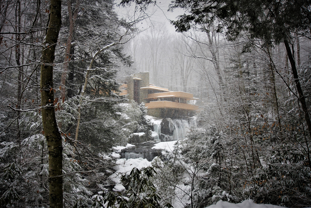 A view of Frank Lloyd Wright's Fallingwater in the snow. You can see the waterfall frozen underneath the house and flowing into the semi frozen river. The house, trees, and rocks in the river are covered in snow. The sky is gray.