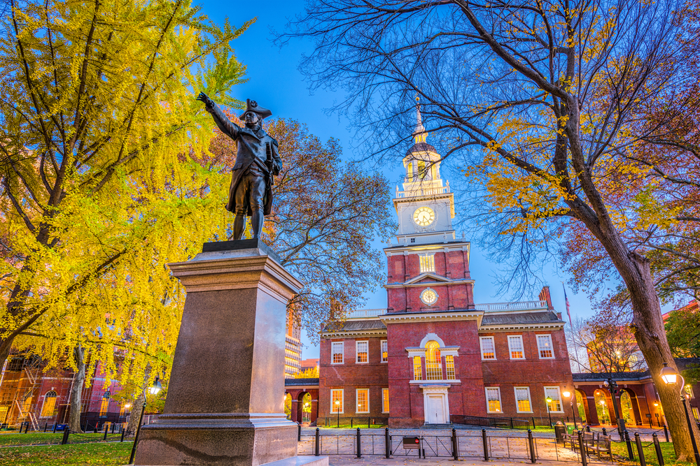 A large brick building that is the Independence Hall, one of the best things to do in Philadelphia. In front of it are large trees, and a statue of a founding father on a marble base.
