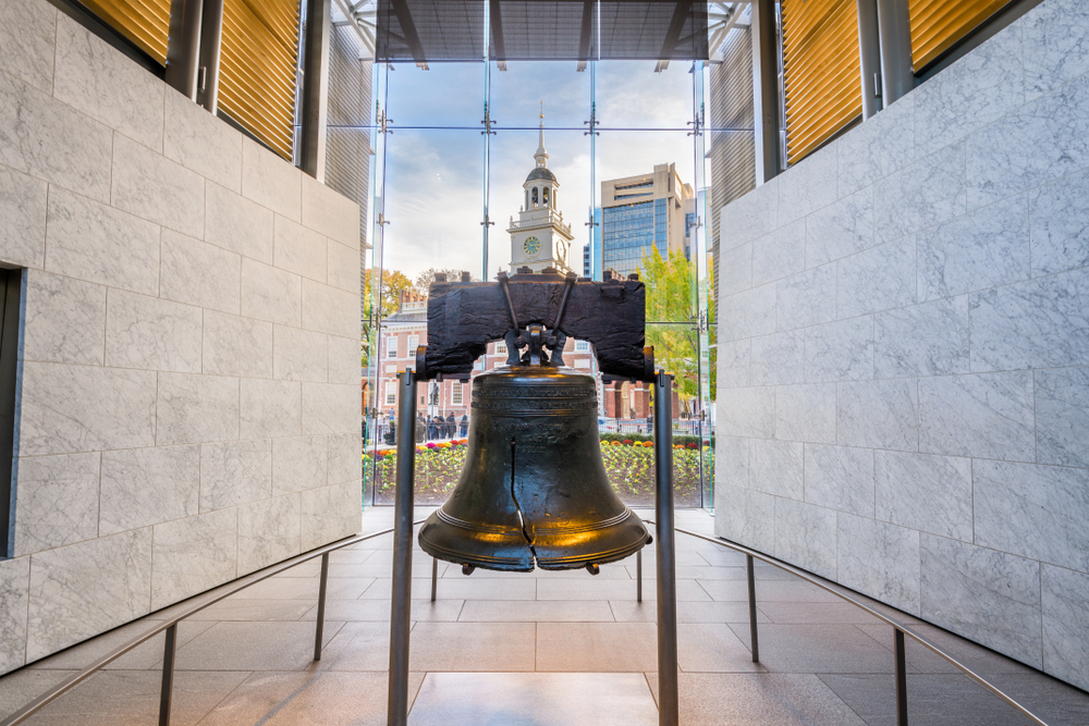 The Liberty Bell on display inside a building in Philadelphia. It is surrounded by marble walls and there is a glass window that looks out onto Independence Plaza.