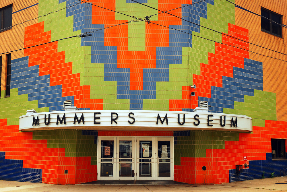 The exterior of the Mummer's Museum in Philly. It is an Mid Century Modern style building that used to be an old movie theater. There is a large mosaic on the front made of red, green, and blue tiles in a chevron pattern up the entire front where the entrance is.