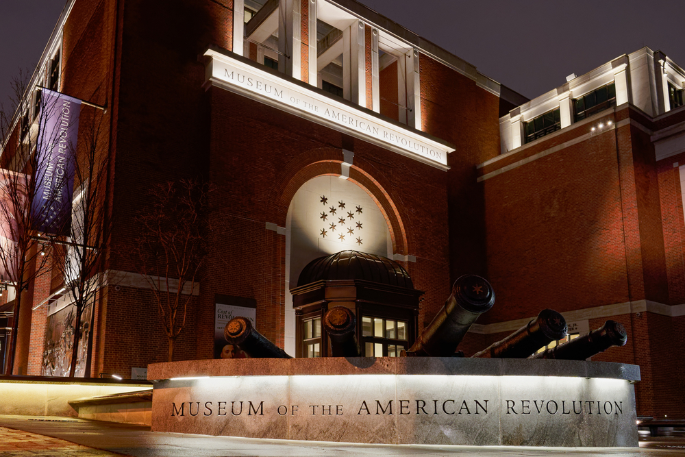 The outside of the Museum of the American Revolution. It is a large brick building. It is night time so parts of the building are lit up.