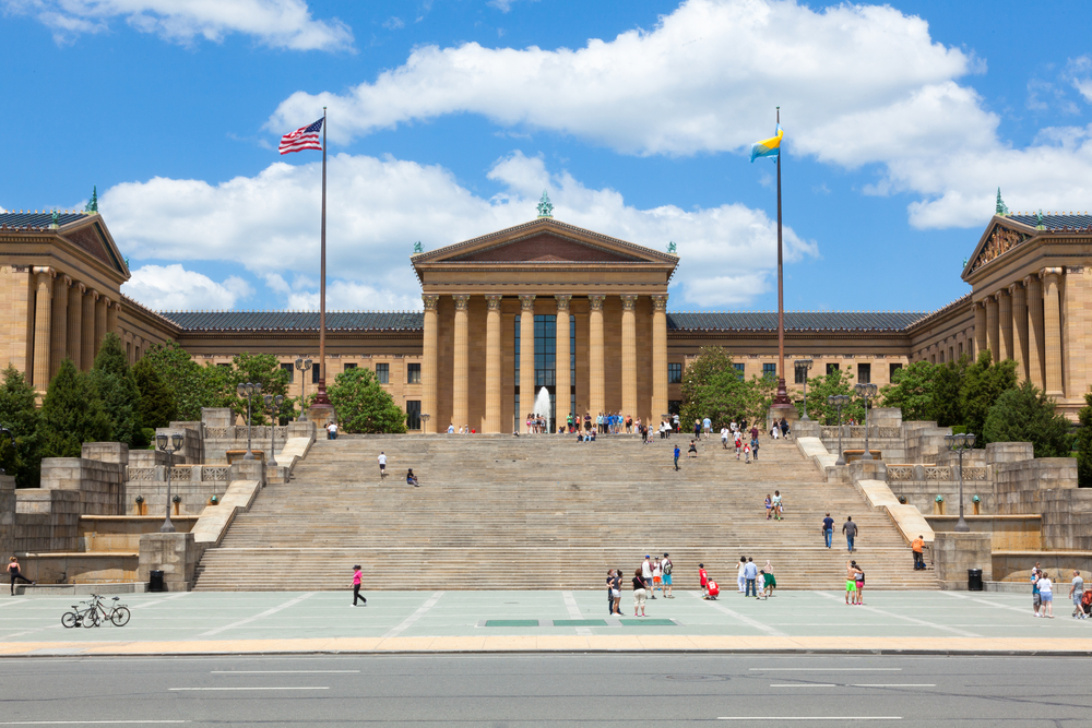 The front exterior of a large ornate Greek style building. It is the Philadelphia Museum of Art. There are large rows of steps in front of it and you can see people walking around.