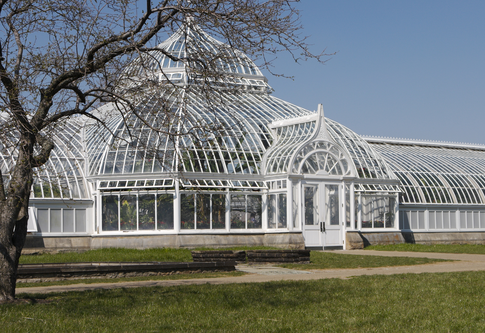 The exterior of the Phipps Conservatory. It is an antique building that looks like it is made of white wrought iron or wood. It has floor to ceiling windows and even the ceiling is windows. It has a large center dome with a set of double doors in front of the dome. Its one of the best things to do in Pittsburgh.