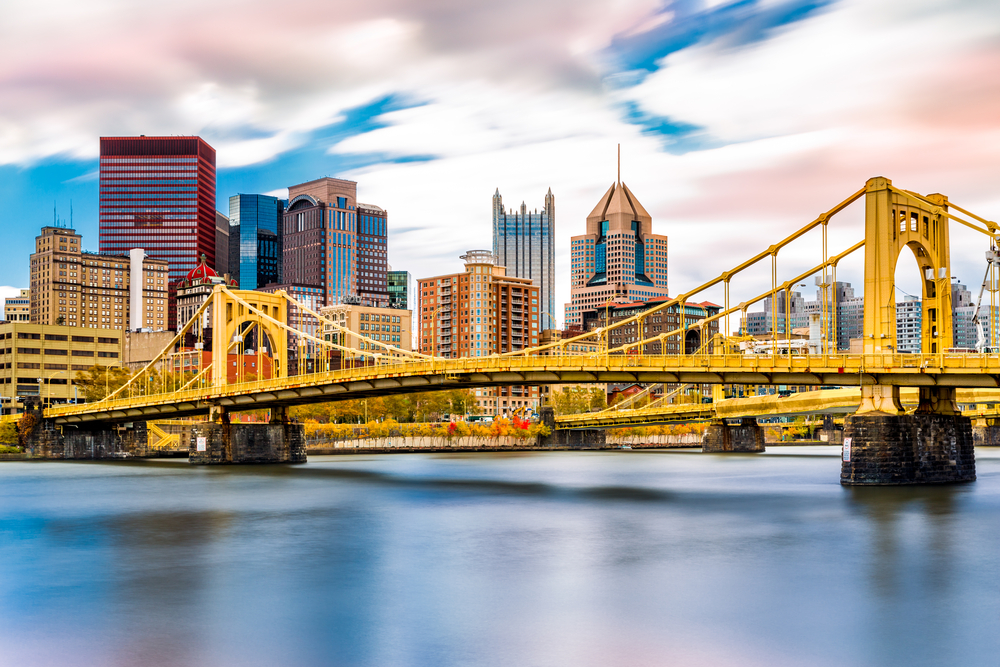 A view of the Pittsburgh skyline from the Allegheny River. You can see two bright yellow bridges crossing the river and skyscrapers.