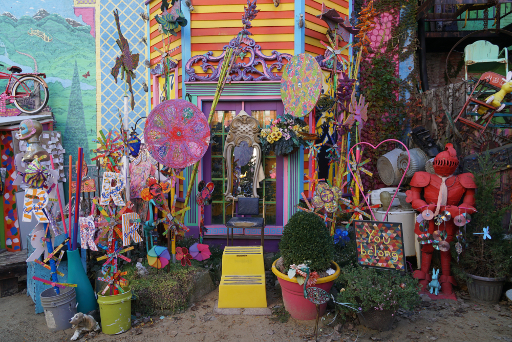 An collection of colorful found objects in front of a wall at Randyland, one of the best things to do in Pittsburgh. There are colorful mirrors, sculptures, chairs, mosaics, and more.