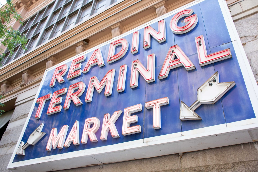 A large blue sign with a red neon sign that reads 'Reading Terminal Market'. There are two white neon arrows pointing down. The sign is on the side of a building.
