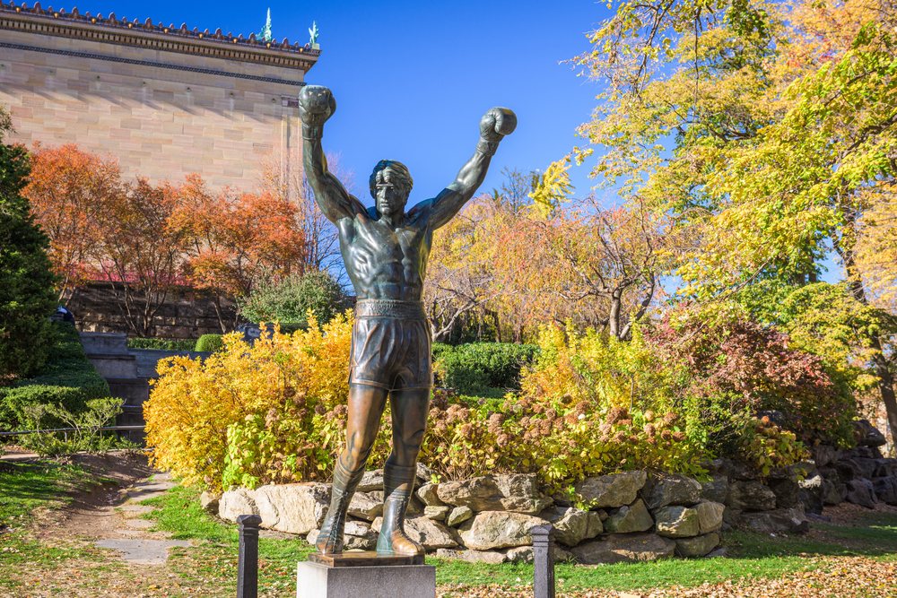 A bronze statue of Rocky Balboa, a character from the Rocky movies. It is one of the best things to do in Philadelphia. Behind the statue you can see lush gardens with grasses, shrubs, trees, and other plants.