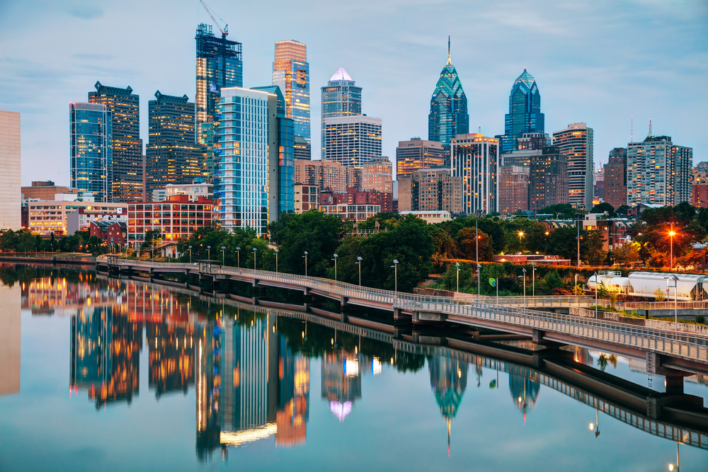 The Philadelphia skyline at twilight. You can see the Schuylkill River next to the city. The city is all lit up and you can see the reflection in the river.