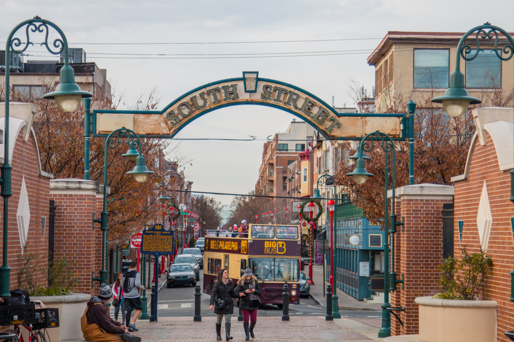The entrance of South Street in Philly. You can see a bus, people walking, and shops down the street. The street is decorated for the holidays so there are wreaths and bright red light poles with garland and ornaments on them.