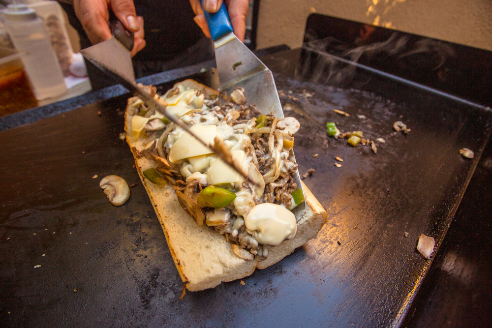 A person using spatulas to place toppings onto a bun. The toppings are a cheesesteak, so there is thinly sliced beef, onion, mushrooms, peppers, and provolone cheese. It's one of the best things to do in Philadelphia.