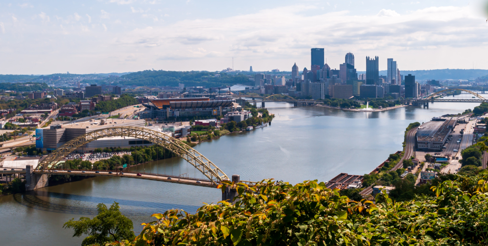 A scenic view of the Pittsburgh skyline, the Allegheny River, and a rounded bridge over the river.
